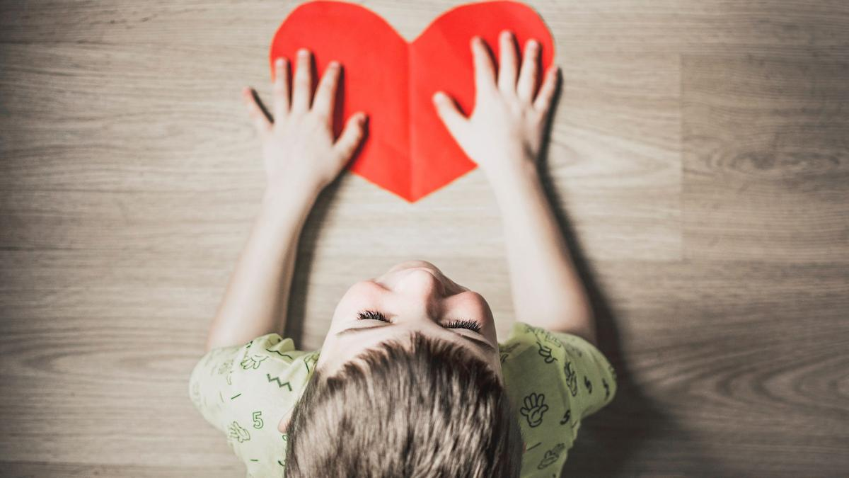 photo looking down above a child's head to a red heart on the floor