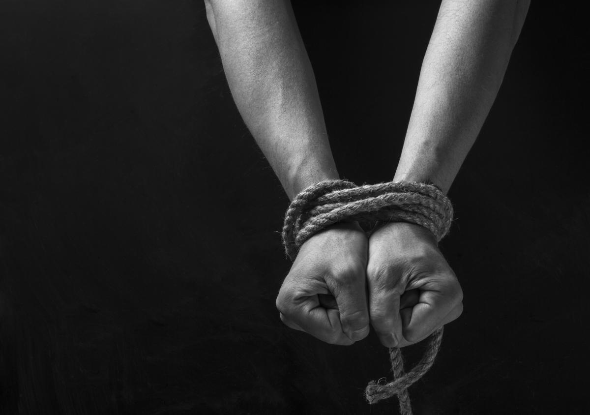 photo of hands tied in rope behind a back